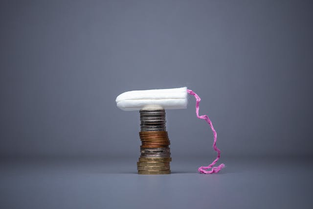 Photograph of an unwrapped tampon resting on top of a stack of British coins. The pink cord can be seem hanging down onto the blue background.