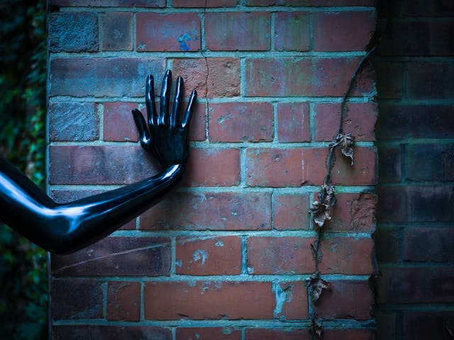 Photograph of a brick wall with the human form of a shiny black hand and arm pressed up against it.