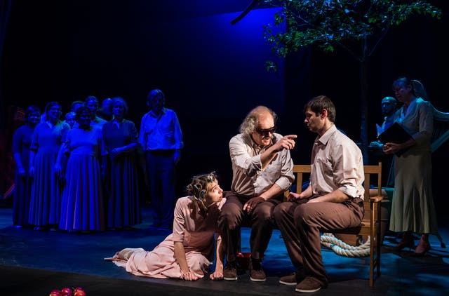 Photograph of a theatre stage. Two male actors are sitting on a bench in the foreground, facing the audience. At their feet is a third actor with curlers in her hair. The actor on the left is wearing dark glasses and pointing towards the actor on the right. In the background, a group of other actors are dimly lit by a dark blue light.