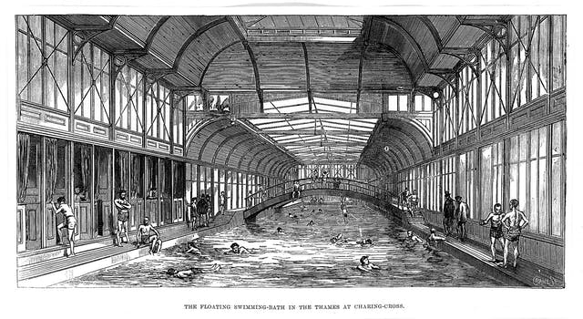 Black and white engraving of the inside of a swimming bath featuring a bridge and people diving, swimming, and standing or paddling at the edge. Some of the spectators are wearing top hats.