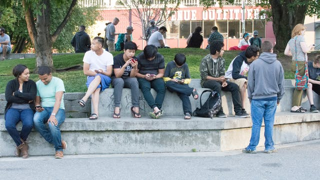 A group of people sitting on a concrete bench in a park, some of them looking intently at mobile phones.