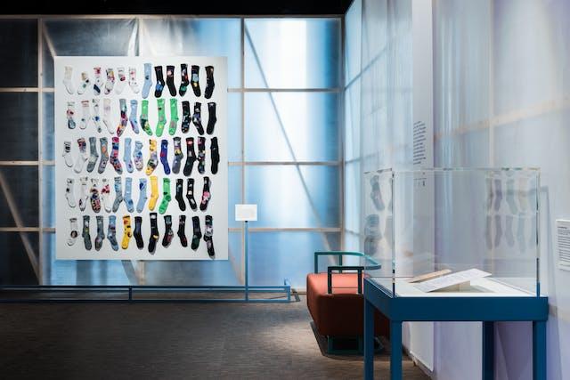 画廊空间的一张照片,展示了半透明的织物背光墙,揭示了后面的木结构,上面挂着一个大的矩形白板。在这块板的前面,60只彩色袜子被安装在一个12横5高的格子里。这些袜子的色调从左边的浅白色调到右边的深黑色调。在图像的右边是另一堵墙,与远墙成直角。在这面墙的前面是一个长凳和一个玻璃展示柜,里面有两个平面的纸展品。