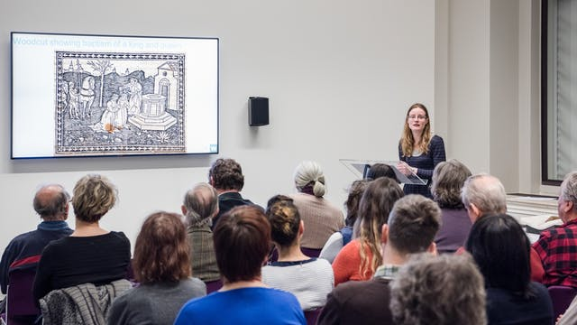 Photograph of a female speaker giving a  presentation to an audience. On the wall is a large screen showing an engraving.