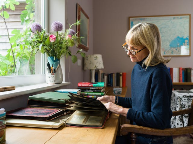 A photograph of a blond women looking through a photo album and sitting on a wooden chair at a desk next to window. On the desk are piles of old photo albums and on the window sill are a flowers arranged in a vase.