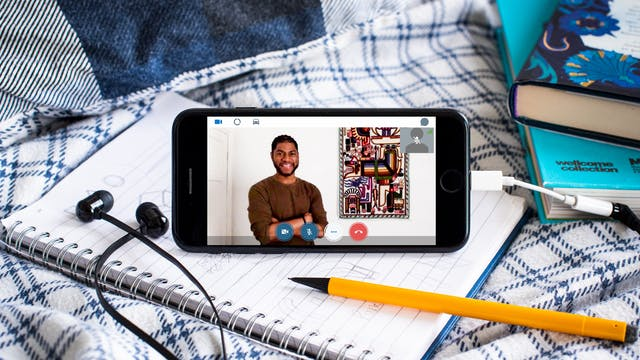 Photograph of a smartphone propped up on a duvet and notebook. Plugged into the phone is a pair of black earbud headphones. On the screen of the phone is a video call with Alain