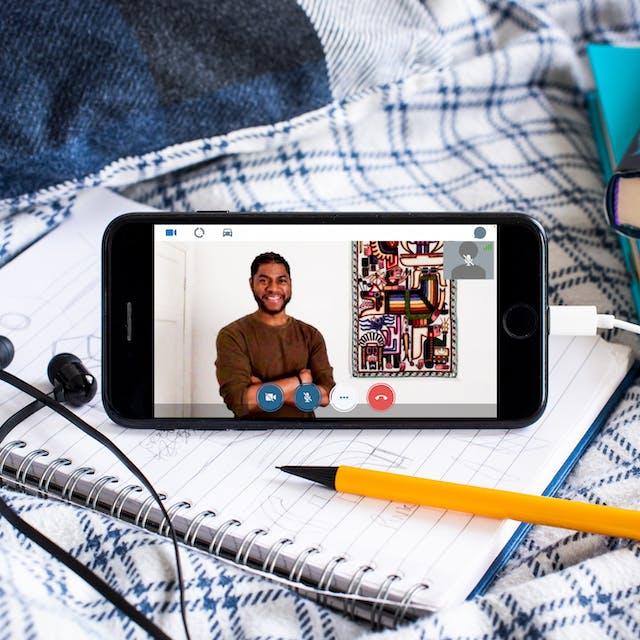 智能手机的照片在羽绒被和笔记本招呼。插入手机是一对黑色耳塞耳机。在手机的屏幕上是一个与Alain的视频通话