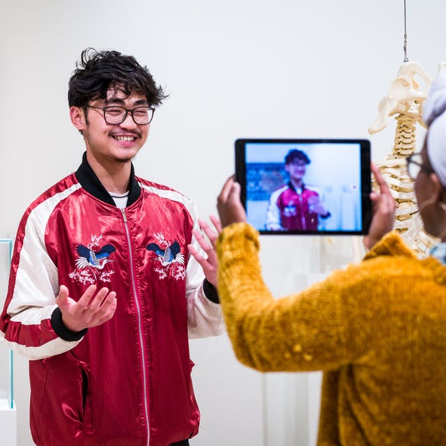 Photograph of a young man and woman using an iPad in the Medicine Man gallery to film each other talking to camera.