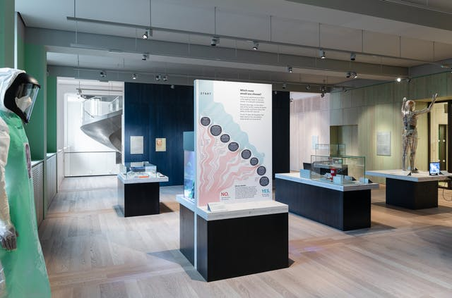 A photograph showing the Being Human exhibition space with windows overlooking Euston Road to the left of the room and the Wellcome Collection Dynamic Stair, seen in the background through the open entrance, also on the left. A wooden panelled wall between the open entrance on the left and an open entrance on the right is painted dark blue and some exhibits are displayed on it. A life-size model wearing a visor and protective clothing is seen in the foreground on the left, and in the middle distance on the right a life-size transparent woman showing internal organs is displayed standing on a table with her arms raised above her head. Central to the image is a wooden table top on a black plinth with a freestanding rectangular backboard with light pink and blue graphics. Text is displayed in eight dark blue circles that run diagonally across the board.