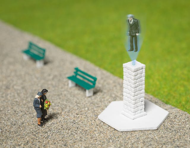 Photograph of model railway scenery depicting a park scene with grass and a wide path. There are two benches and a tall white brick monument. A model of two small figures holding a wreath stand in front of the monument. Out of the top of the monument is a projected holographic image of a man in a suit and tie, looking towards the figures below.