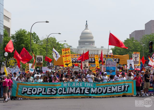 Lots of people holding brightly coloured banners and flags on a climate change march in Washington, with the Capitol building in the background.