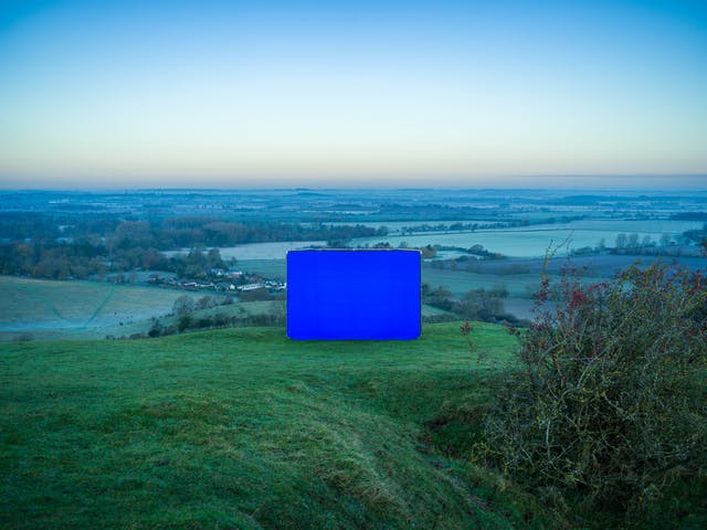 显示山顶景观的彩色风景照片。这张照片是在黎明时分拍摄的,风景给人一种霜冻的感觉。图像的中心是一个大的矩形摄影背景框。整个框架采用活力四射的蓝色chroma key面料。画面是站在山顶上的草丘上。屏幕后面是远处的景色,包括田野、小建筑物和地平线。地平线上的天空是一种迷人的色调混合,从地平线上温暖的金色色调混合到天空向上延伸时充满活力的蓝色色调。在前景右侧是一个不整洁的树枝状灌木,依偎在一个山谷中。