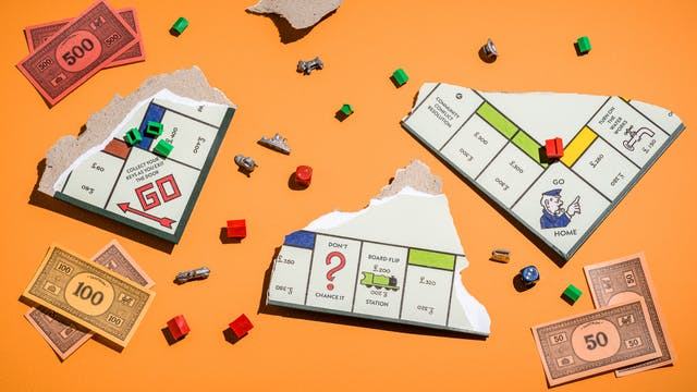 "Photograph of a ripped up board game where three board pieces are visible, facing upwards.  scattered around the orange table are pieces of the board game, including  green houses, red hotels, the board pieces and some fake money.  The game title in the money reads ""Tantrum"".  Other squares on the board game read ""Collect your keys as you exit the door"", ""don"