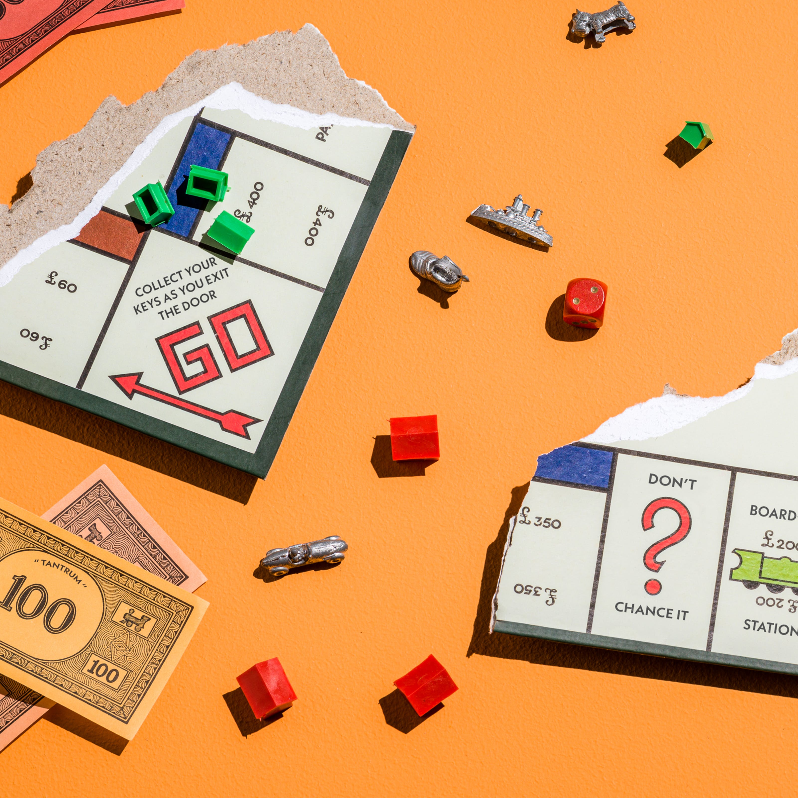 "Photograph of a ripped up board game where three board pieces are visible, facing upwards.  scattered around the orange table are pieces of the board game, including  green houses, red hotels, the board pieces and some fake money.  The game title in the money reads ""Tantrum"".  Other squares on the board game read ""Collect your keys as you exit the door"", ""don't chance it"", ""board-flip station"", ""community conflict resolution"", and ""turn on the water works""."