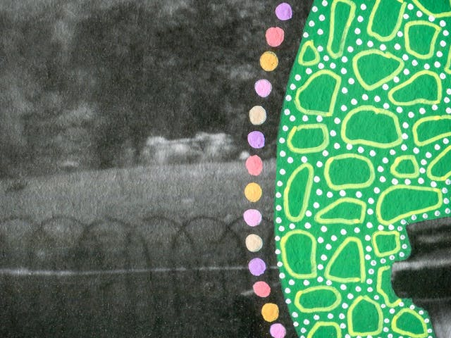 Artwork created by painting over the surface of a black and white photographic print with colourful paint. The artwork shows the original scene of a parkland scene with a black hooped fence separating the path from the planted grass area. Entering the frame on the right is part of a large oval shape painted green, which is covered in small lighter green dots and many organic shaped circular light green outlines. Around the edge of the oval shape are a line of coloured painted spots, of yellow, pink and purple. The texture of the paint can be seen on the surface of the print.