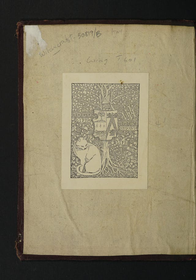 Inside cover of a book with a bookplate depicting a cat sitting beneath an apple tree.  A shield with a coat of arms on hangs from the tree.  Adjacent to the tree are the words