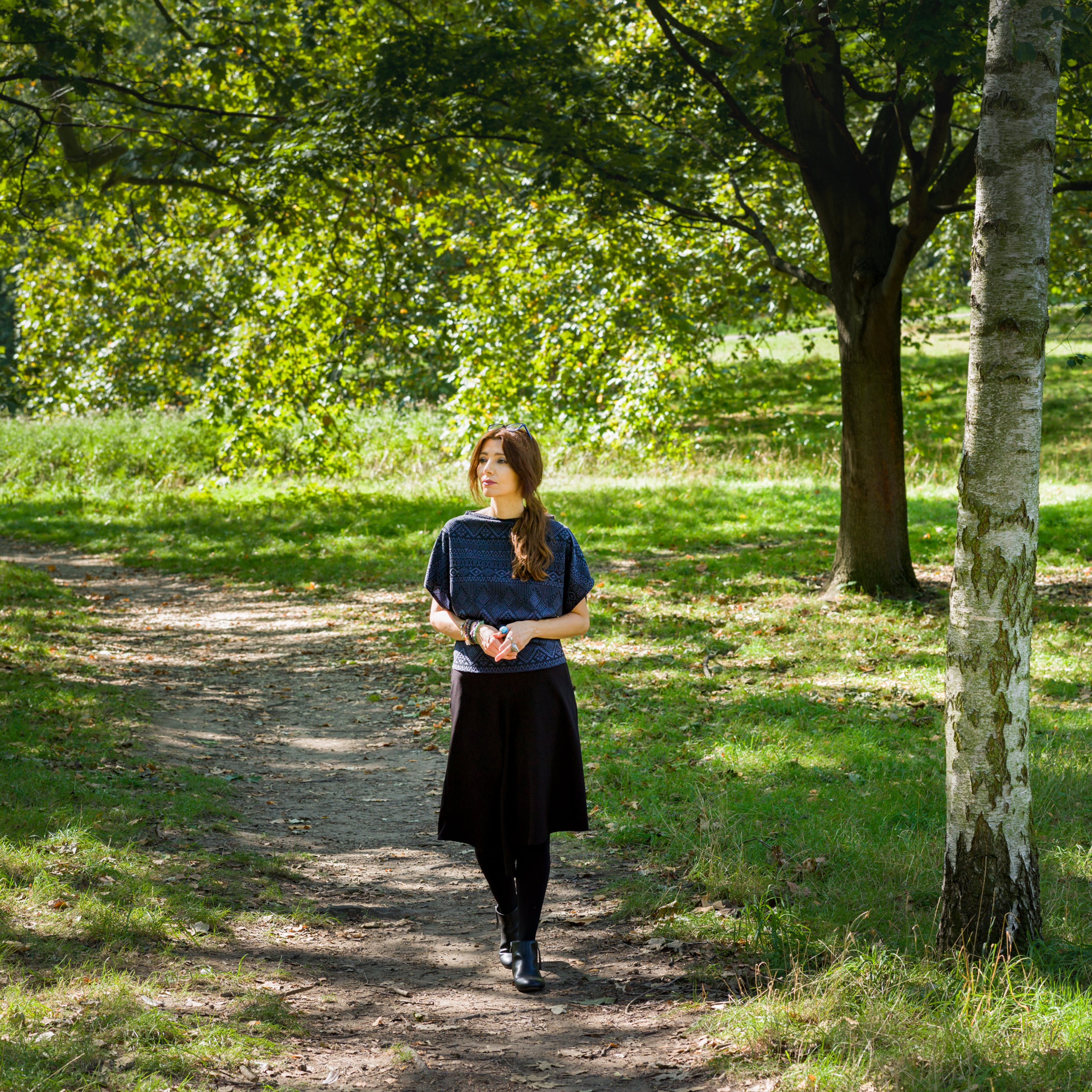 Photographic full length portrait of a woman outside in a woodland scene. She is walking along a rough footpath towards the camera, fingers loosely clasped together. She is looking off to the left. To her left are a series of tree trunks and surrounding the path and the in the background is the green of the grass and leaves of the trees.