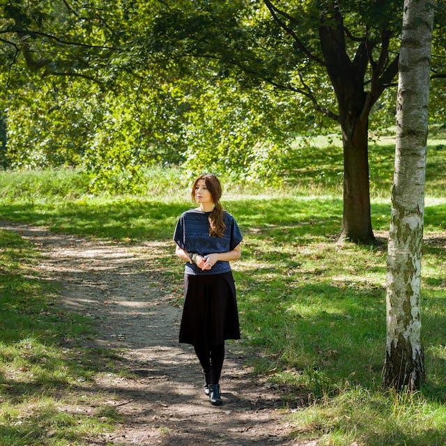 拍摄一个女人的全身肖像在外面的林地场景。她沿着一条粗糙的小路走向镜头,手指松松地紧握在一起。她往左边看。在她的左边是一系列的树干和周围的道路,背景是绿色的草和树叶的树木。
