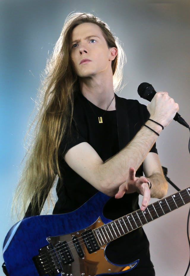 Photo of man with long hair holding a microphone and a guitar.