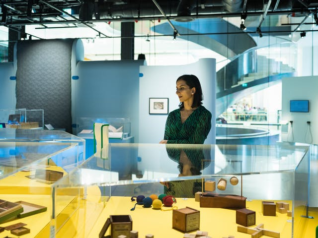 Photograph of a woman in an exhibition gallery space standing behind a glass display case. In the display case are wooden puzzle objects and wooden balls.