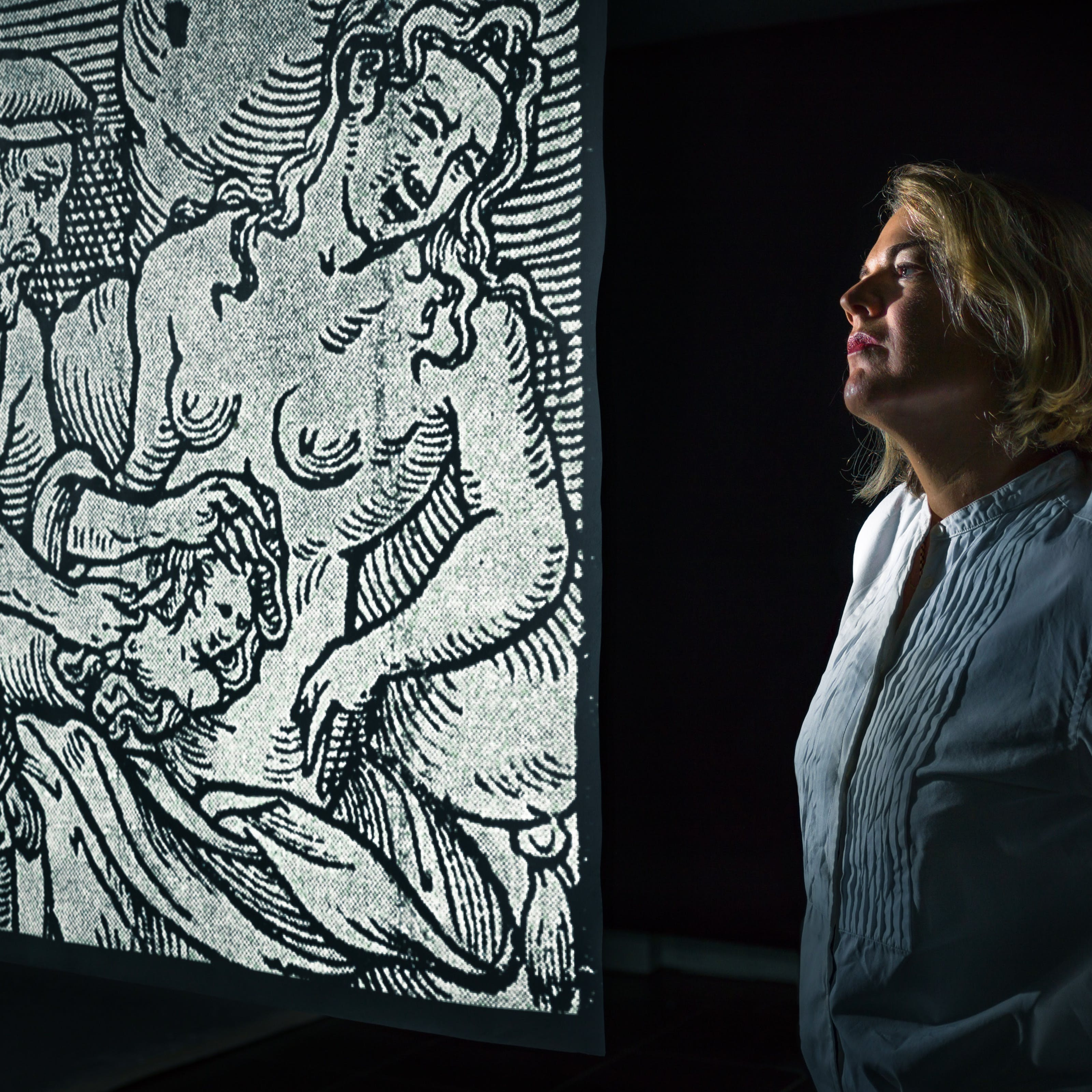 Photograph of Anna Blundy stood by a projected image of an engraving.