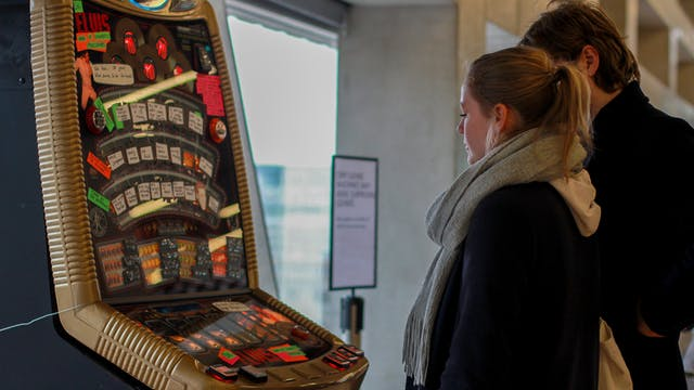 Two people standing in front of a DIY hacked Crip Casino fruit machine.