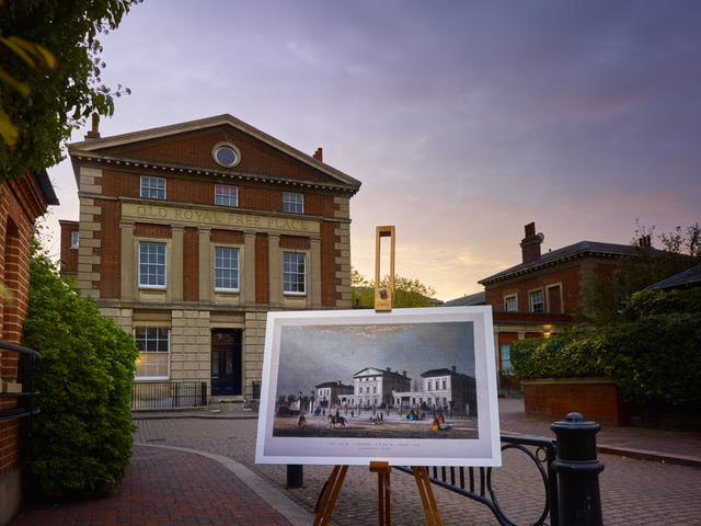 Photograph of the former New London Fever Hospital with an historical image of the hospital displayed in front of it on a wooden artist