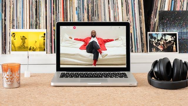 桌上的笔记本电脑的照片。笔记本电脑屏幕上有一幅哈罗德·奥菲(Harold Offeh)的肖像,他坐在沙发上,双臂摊开在沙发背上,双腿交叉。哈罗德戴着眼镜,穿着红夹克和白衬衫。笔记本旁边放着耳机和一张明信片,上面是《我们眼泪里的欢乐》(Joy Inside Our Tears)的剧照,四张表演者的照片,每一张都用明亮的黄色调叠加在一起。