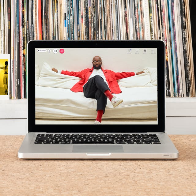 Photograph of a laptop on a desk.  On the laptop screen is a portrait of Harold Offeh sitting on a sofa with his arms spread out across the back of the sofa and his legs crossed. Harold is wearing glasses, a red jacket, and a white shirt. Next to the laptop are headphones and a postcard showing a still from Joy Inside Our Tears, four photographs of performers each monotone with a bright yellow tone overlayed.