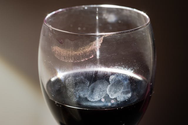 Photograph of wine glass containing red wine. on the surface and around the lip of the glass are lipstick and finger print marks.