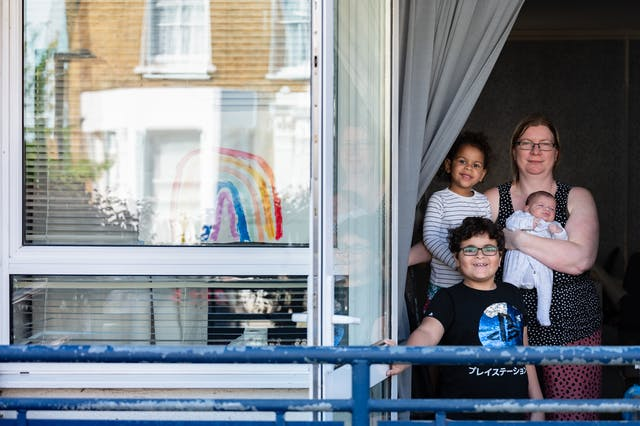 Photograph of a mother and her 3 children stood in the open door of their home, smiling to camera. In their window to the left is a hand painted picture of a rainbow.