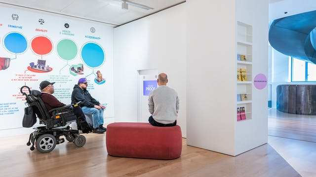 Photograph of a gallery installation with three seated people watching a video on a tv screen. On the wall to the left are large bold graphics and text, coloured blue, red and green. To the right are leaflets standing on 5 shelves, inset into a wall. In the distance are the windows and a section of a spiral staircase.