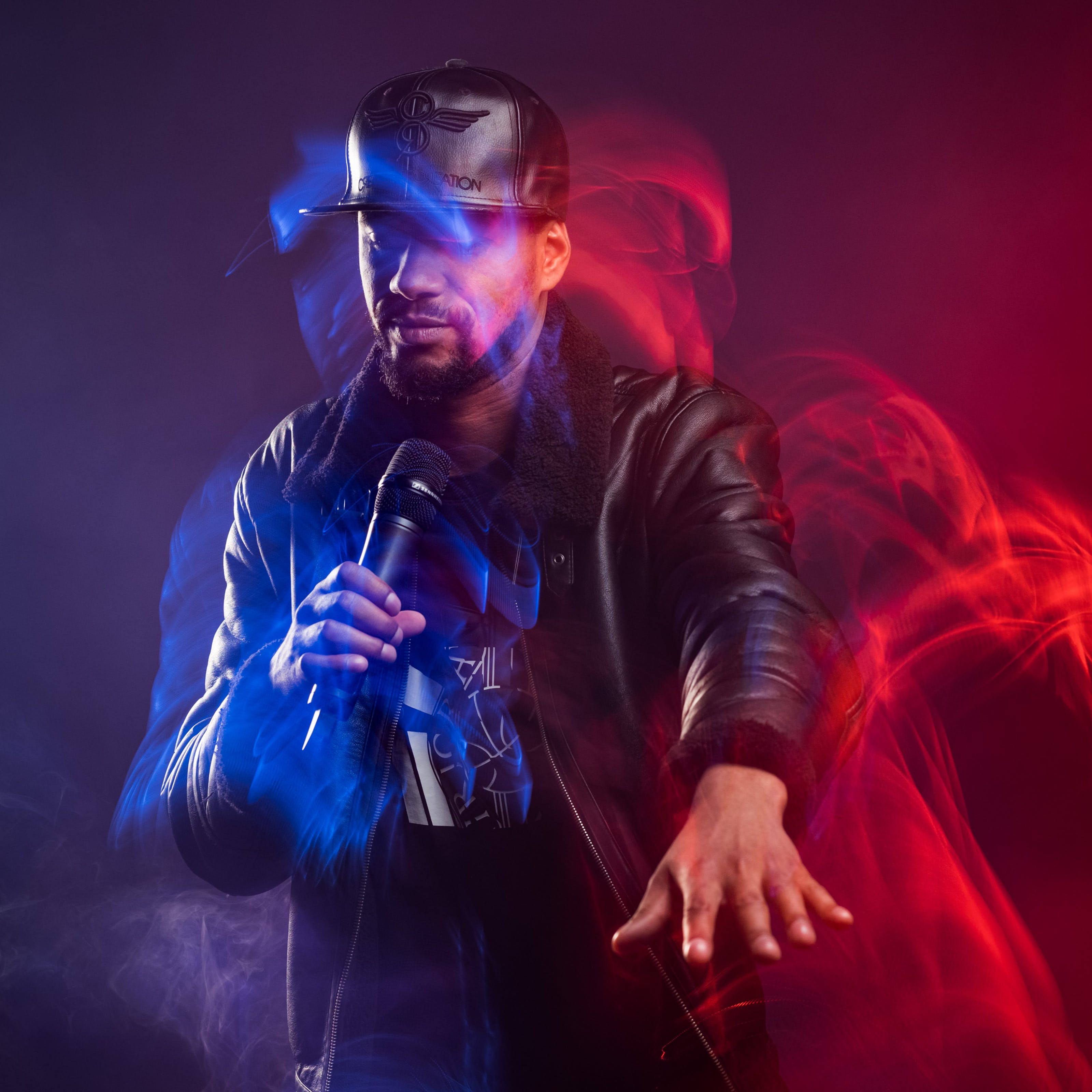 A male rap artist dressed in a black leather hat and jacket is holding a microphone, dancing with his arm outstretched in front of him. The room is filled with smoke and blue and red lighting effects highlight his movement.