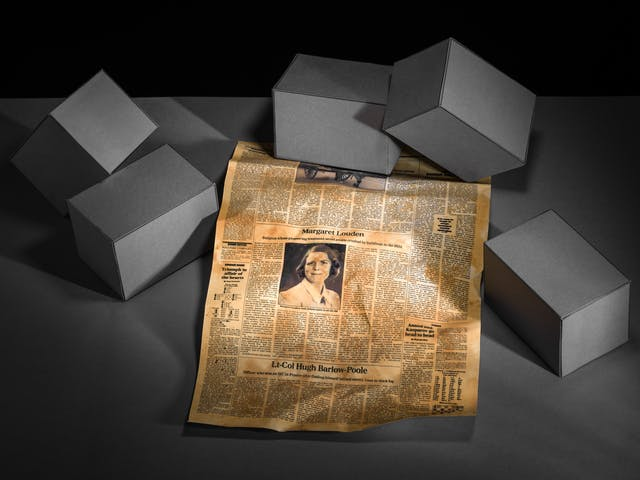 Photograph of a set-built scene made up of a grey card horizontal base against a black vertical background. The view looks down on the surface where there are five rectangular brick blocks scattered in a random arrangement which are also made out of grey cardboard. In the centre of the image and tucked under a couple of the blocks, is an obituary page from a newspaper. It is crumpled and yellowed with age. In the centre of the newspaper is an obituary with a portrait of a young woman with short hair wearing a blouse. Above the portrait is the name Margaret Louden.