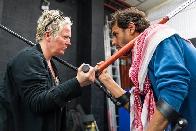 Photograph of a man and a woman in a rehearsal space facing each other in a theatrical expression of competitiveness. Each person is holding a crutch over the shoulder of the other.  The arms and crutch of each person overlap and form an X at the centre of the frame.