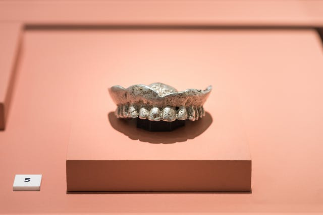 Photograph of an upper set of aluminium dentures in an exhibition case.