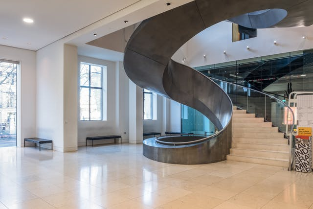 A photograph taken at the foot of a broad architectural staircase called with a steel balustrade. The stairs rise from the atrium to the first floor and beyond with a glass wall beyond it on the same floor serving as an exhibition space.