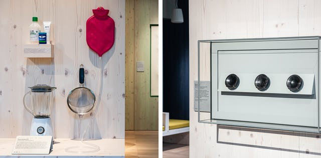 Diptych. The photo on the left shows a wooden panelled table top on which sits a food blender. A wooden panelled surround holds a small shelf on which sterile eye wash, VapoRub, and KY Jelly sit. To the right, hanging from a hook, is what resembles a pink hot water bottle with a valve at the bottom with a long clear plastic tube attached and trailing down the backboard onto the wooden table top. The photo on the right shows a glass case mounted on a wooden panelled wall containing three black marble like palm sized plasticised blood dishes in a line.
