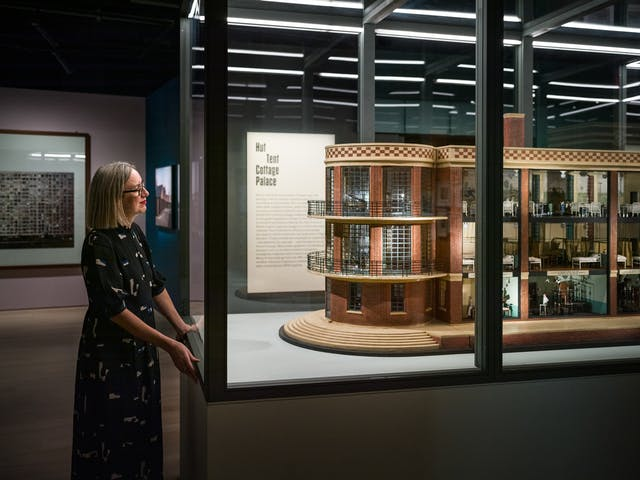 Photograph of curator Emily Sargent looking at a large architectural model in the exhibition Living with Buildings at Wellcome Collection.