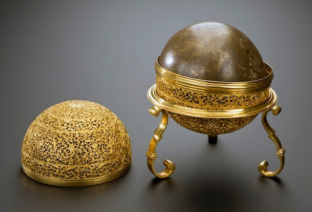 Image of gold round casket with ornate filigree