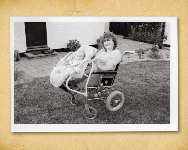Photograph of a black and white photographic print, resting on a brown paper textured background. The print shows a garden scene with a grass lawn and part of a white rendered house and black door. In the centre of the image is a woman seated in a wheelchair. Her arms and legs are short as a result of her mother being prescribed thalidomide when she was pregnant. Attached to the front of her wheelchair is a baby carrier with a small baby strapped in. Both are looking towards camera, the mother smiling.