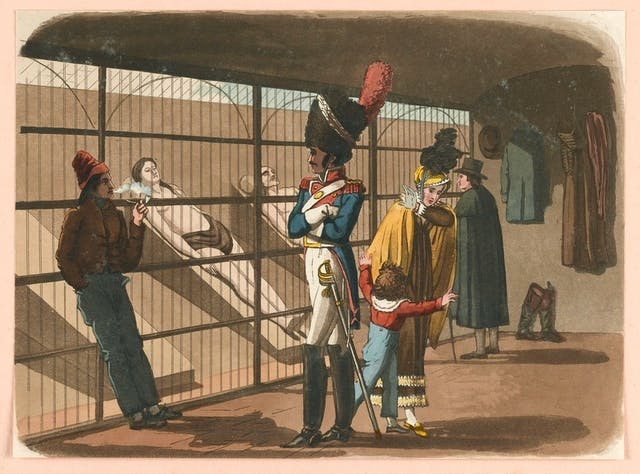 Colour painting of people in a morgue in Paris. Two cadavers are visible behind railings, with a soldier looking on and a woman with a young child turning away.