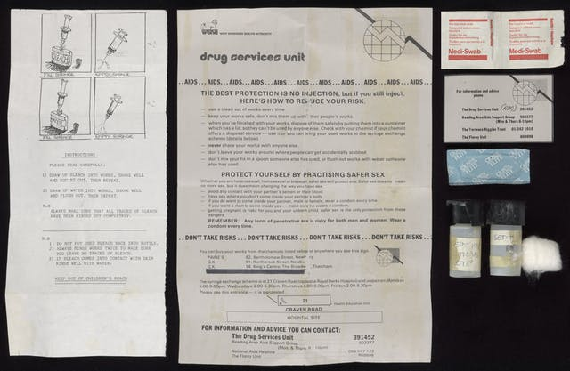 A number of items photographed against a black background, including two black and white leaflets, two medi swabs, a condom, two small screw lid containers, a cotton wool ball and a card with helpful telephone numbers listed on it.