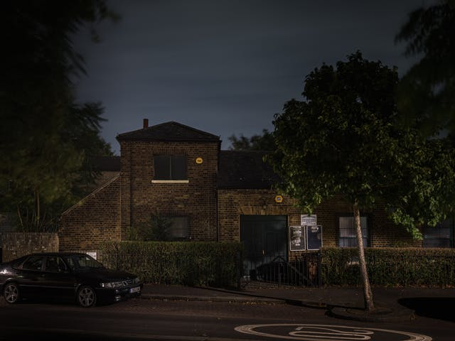 Photograph of the National Spiritualist Church, Walthamstow, at night.  The building is set amongst dense foliage with very little light making its way onto the facade of the exposed brick building.  A single car can be seen in the foreground,