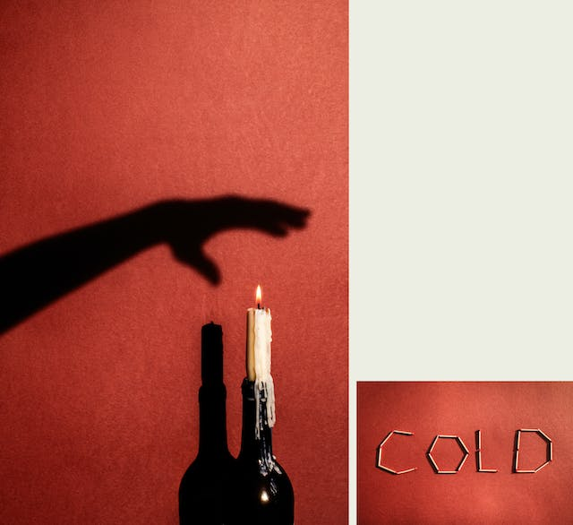 Photographic diptych, one large vertical image on the left and one smaller horizontal image on the right. The one on the left shows a burning candle in the neck of a wine bottle with melted wax running down the candle onto the bottle. Behind the bottle is a red background where a hard light is casting the shadow of bottle and candle. Above the candle on the background is the shadow of an arm and hand outstretched as if being held over the flame. The image on the right shows the word