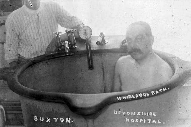 Black and white photograph of a moustachioed man sitting upright in a bath. Behind him stands someone in a blouse leaning on their elbow beside some taps and gauges.