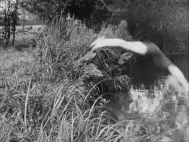 Black and white still from a film showing a man diving from a grassy area into a pond.