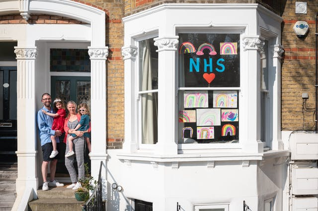 Photograph of the front of a Victoria house showing the front door and bay window. In the doorway stands a father and mother holding their two children. Stuck to the bay windows are hand drawn pictures of rainbows and the letters, NHS with a red heart.