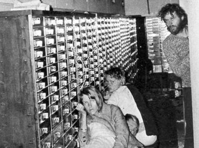 Three people chained to a telephone exchange, and a man with a beard.