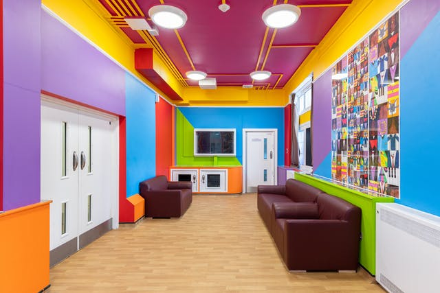 A photograph showing t a long, narrow and brightly coloured room containing a wall-mounted television, and three brown faux leather sofas. The walls are broken up into large purple, blue, red, green and yellow rectangles and triangles. The ceiling is painted purple, with housed wiring painted bright yellow running between the edges of the room and four lights. On the wall behind two sofas, is a square mural made up of lots of smaller squares featuring simple brightly covered graphics including piano keys, clothed torsos, and picture frames. Similar images run along the top of a narrow cupboard below.