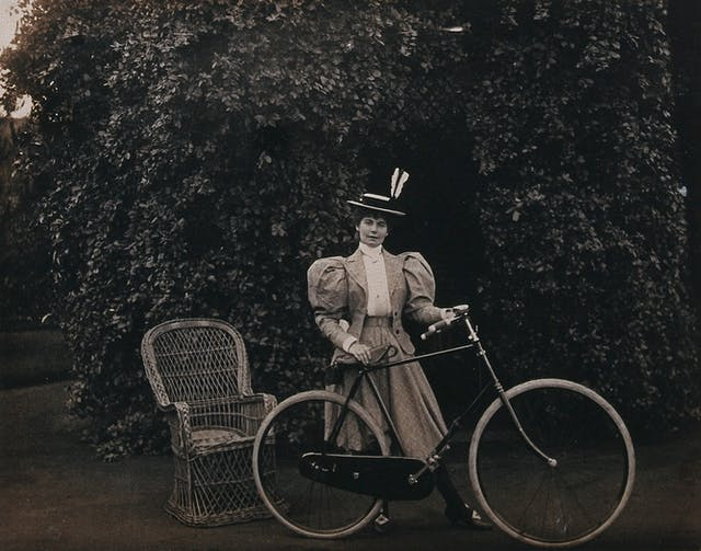 Black and white photo of a woman with a bicycle with bushes in the background. The sleeves on her jacket are puffy and she has two white feathers in her straw boater hat.